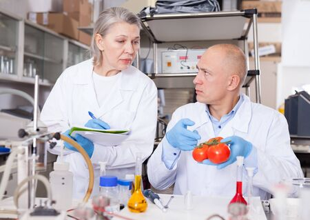 Scientific researching in laboratory. Two scientists taking notes while checking quality and purity of agricultural products