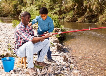 Portrait of cheerful afro man and his little son fishing with rods on river