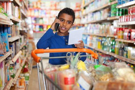 Focused serious African tween boy talking on phone and looking at shopping list while visiting supermarket