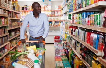 Positive African American man making purchases in grocery store, pushing full shopping cart