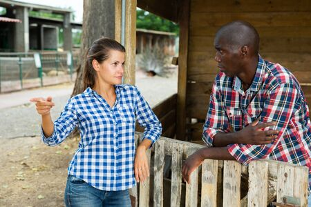 Worried woman standing behind wooden fence near farmhouse, having unpleasant talk with male neighbour Stock Photo