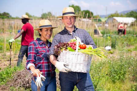 Happy family of gardeners posing with harvest of vegetables in garden