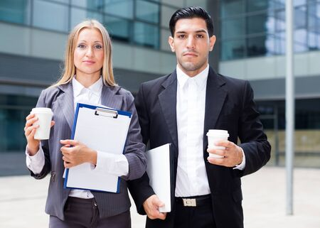 Businesswoman and her partner are standing with folder and coffee near the office. Foto de archivo - 150379643