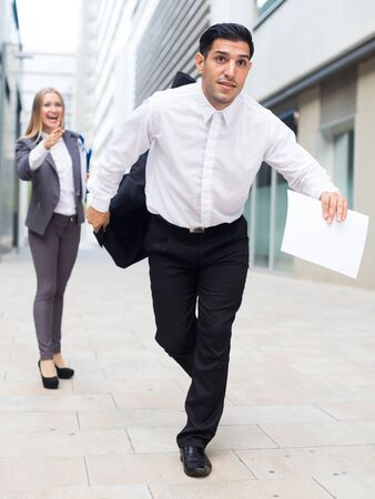 Man is running away from angry businesswoman because she is dissatisfied of the results of the financial report outdoors.
