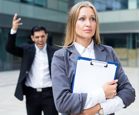 Female employee is upset  with the reprimand of boss near office.