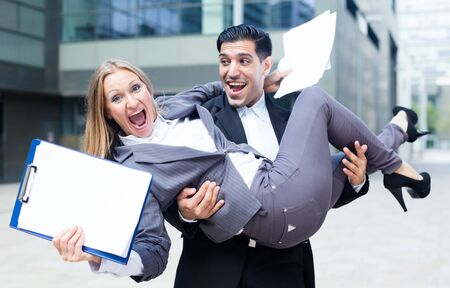 Boss is carry woman manager on hands because they are satisfied of successful contract outdoors near office. Foto de archivo