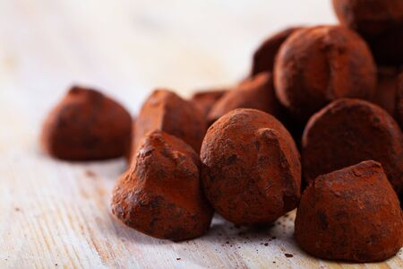 Pile of tasty sweet chocolate candies truffles on wooden background