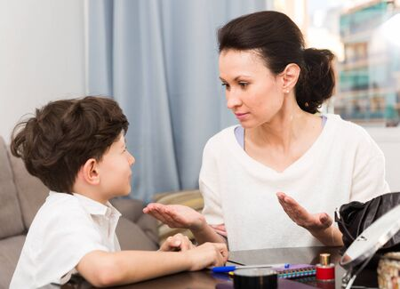 Annoyed mother discussing misbehavior with tween son while they sitting at home table