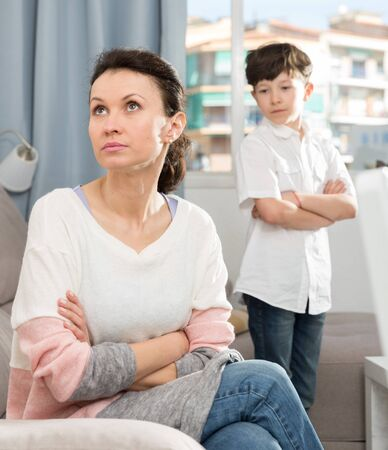 Upset woman sitting and looking away after quarrel with her teenage son Reklamní fotografie