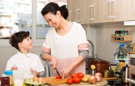 Happy family of young mother and preteen son cooking together at home Stock Photo