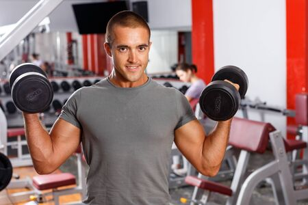 Positive sporty guy doing exercises with dumbbells at sports club