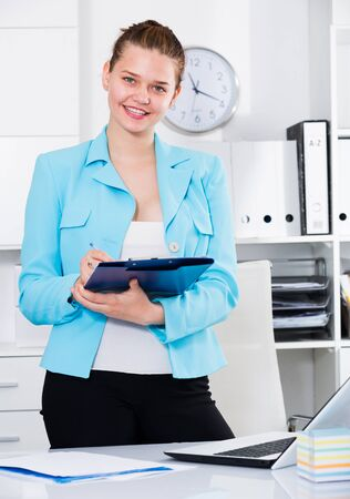 Office worker woman is signing contract at office.