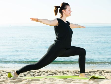 Smiling adult female in black T-shirt is stretching on the beach.