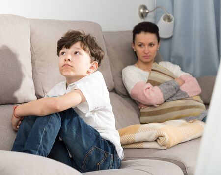 Upset preteen boy sitting on sofa and looking away after quarrel with mother