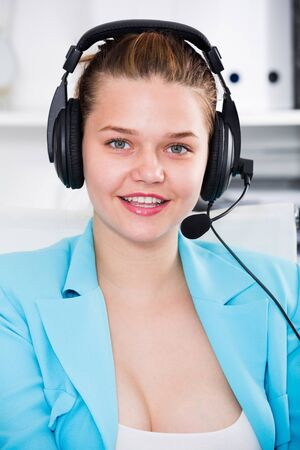 Office worker woman is working at a computer and talking by headset with client in the office.