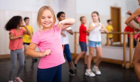 Portrait of little girl doing exercises during group class in dance center