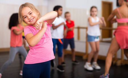 Positive girl exercising in group of classmates during dance class at school