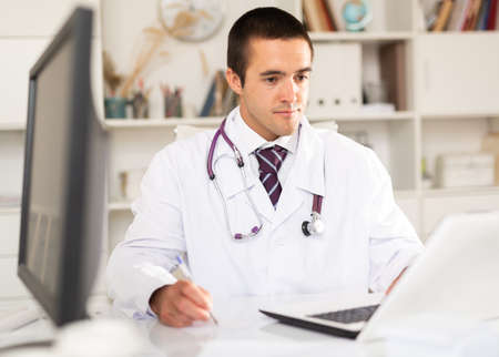 Focused doctor working with laptop in office