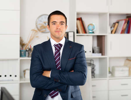Successful businessman with arms crossed in office interior
