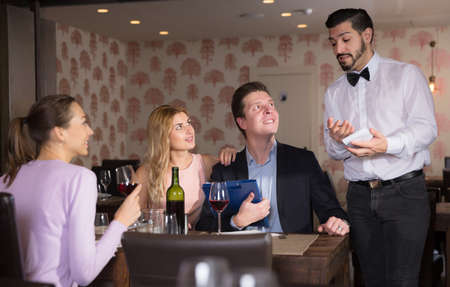 Young waiter taking order in restaurant