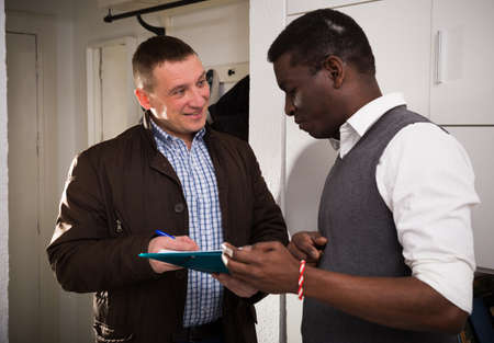 Friendly landlord signing agreement with positive man
