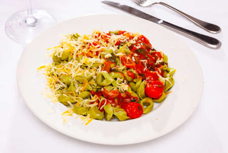 Spinach tortellini served with tomato sauce and greens