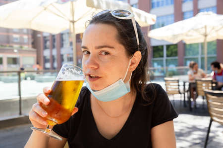 Woman in protective medical mask with glass of beer at bar
