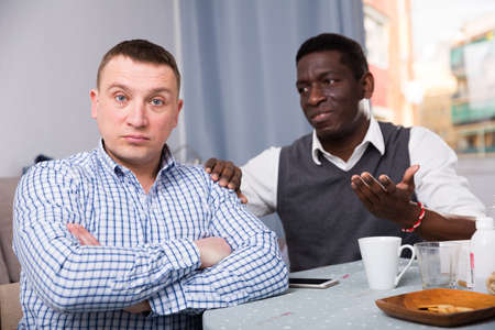 African man calming friend after dispute