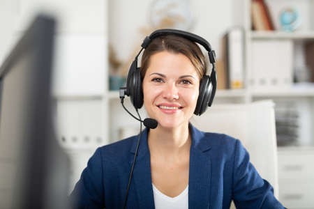 Office worker woman is working at a computer and talking by headset with client Foto de archivo