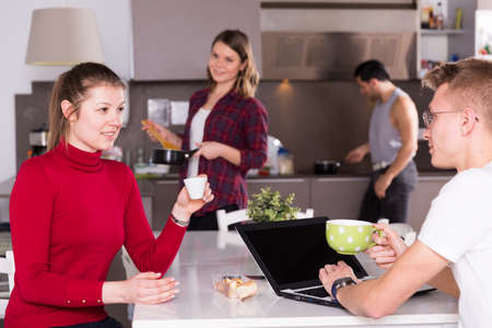 Female helping guy to plan tourist itinerary at hostel kitchen