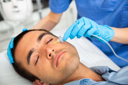 Male client getting carbon dioxide injections for face skin