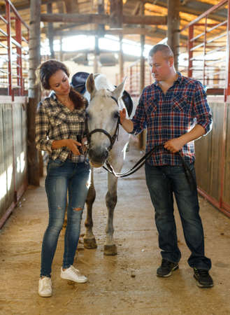 Smiling couple with white horse standing at stabling indoor Фото со стока