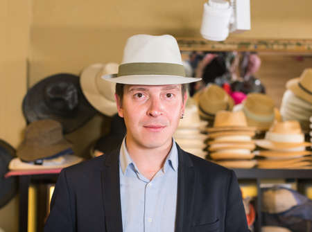 portret of smiling guy try on panama at headwear store Stock Photo