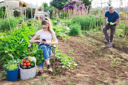 Teenage girl addicting in phone on family vegetable garden