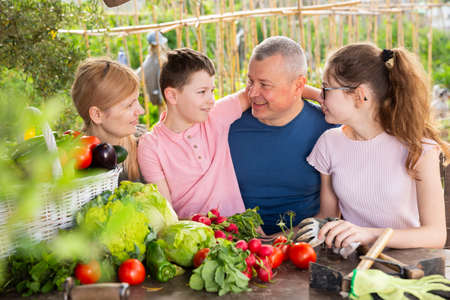 Family talking in garden with gathered vegetables