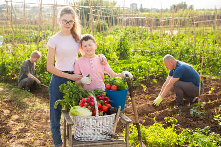Girl and boy posing in garden with harvest