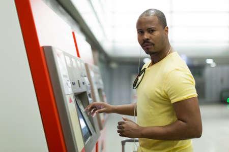 Young man purchasing ticket at terminal in subway platform