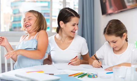 Mother and two children together with wax crayons