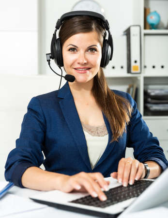 Office worker woman is working at a computer and talking by headset with client in the office Foto de archivo