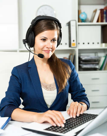 Smiling young female operator talking with customer using headset at company office