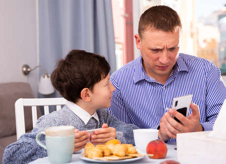 Young man and his son using phones at table with tea indoors