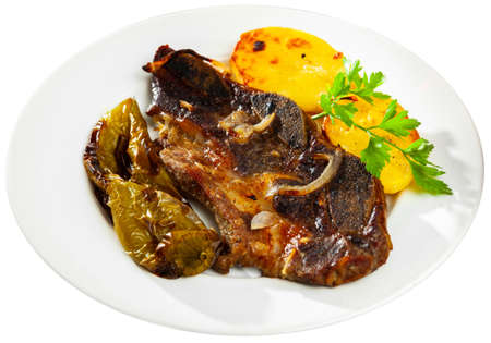 Roasted beef meat on bone with baked potatoes and pepper