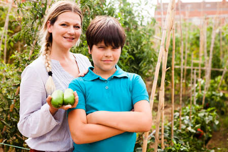 Woman gardener holding cucumbers and little boy standing together in garden