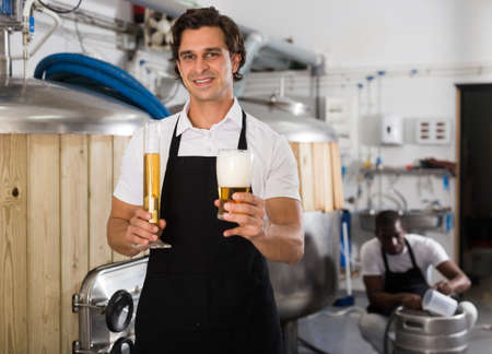 Man brewer in uniform is standing with glass of beer and flask Banco de Imagens