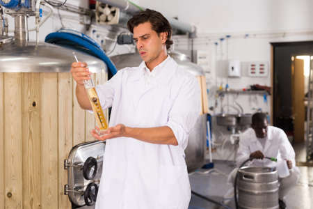 Young man brewer controlling quality of beer in flask in brew-house