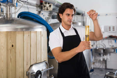 Worried expert is standing with flask for beer and analizying quality
