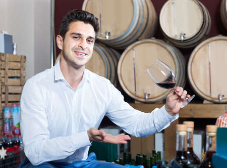 portrait of man tasting wine sample in glass in alcohol section with woods