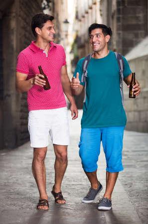 Male fans walking with beer Фото со стока