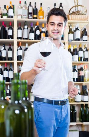 portrait of man tasting wine sample in glass in shop