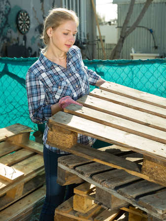 Woman laying wooden pallets